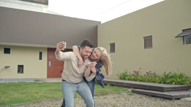 Latin couple takes a selfie outside their new house showing their house keys
