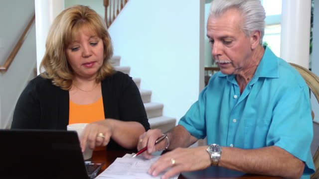 Latin Couple Work on Home Finances with Laptop- WS video