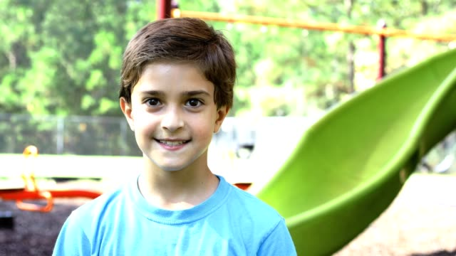 Latin descent boy playing on school playground. Latin descent school boy playing on playground. He gives thumbs up as other children run by him.  Education in USA, exercise themes. one boy only stock videos & royalty-free footage