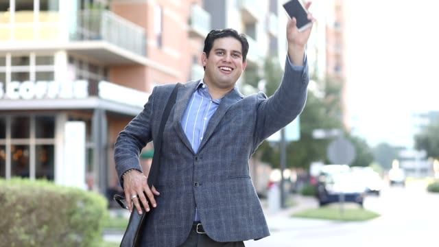 Latin descent business man in downtown city waiting on crowdsourced taxi. video