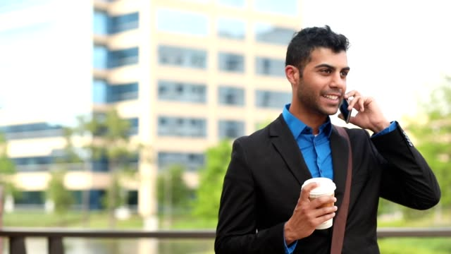 Latin descent business man on the go in downtown city. video