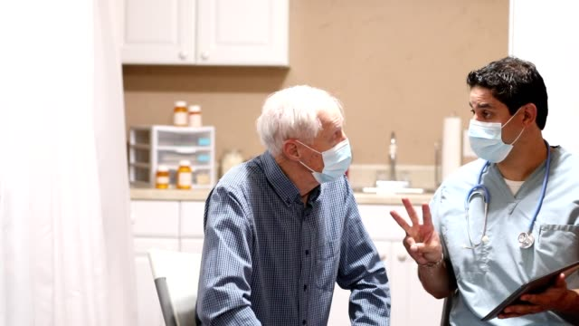 covid-19: latin descent doctor and senior adult patient, masks. - ambulatorio medico video stock e b–roll