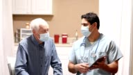 istock COVID-19: Latin descent doctor and senior adult patient, masks. 1236725064