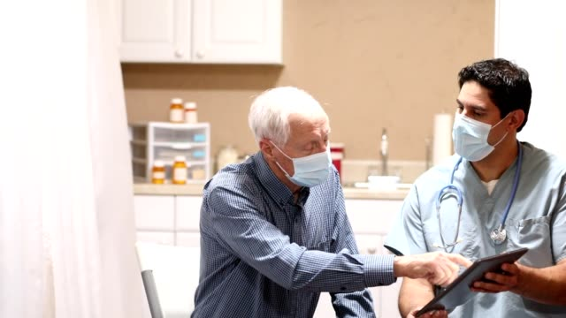 COVID-19: Latin descent doctor and senior adult patient, masks. video