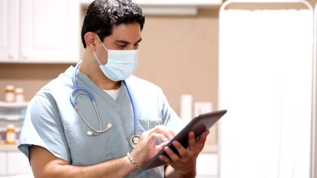 vidéos et rushes de covid-19 : médecin ou infirmière d'origine latine utilise la tablette numérique. - infirmier