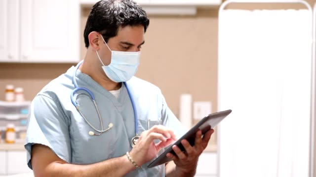 COVID-19: Latin descent doctor or nurse uses digital tablet. video