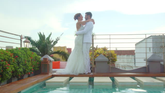 latin ethnic couple celebrating their wedding next to a pool in a hotel while they hug each other excitedly - young couple wedding friends video stock e b–roll