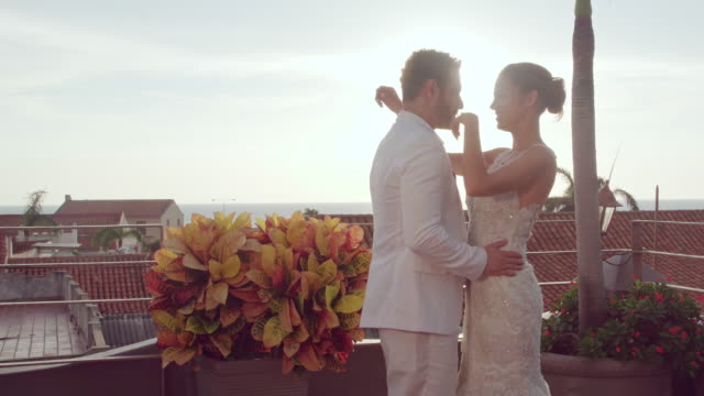latin ethnicity couple celebrating their rooftop wedding, hugging each other enthusiastically while kissing and looking in love - young couple wedding friends video stock e b–roll