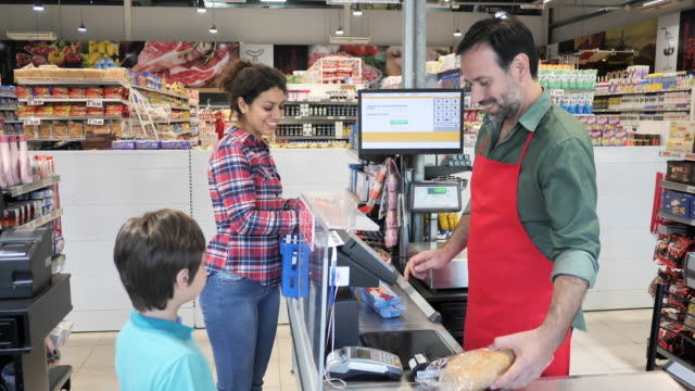 Latin family shopping in supermarket - adult woman paying with contactless card
