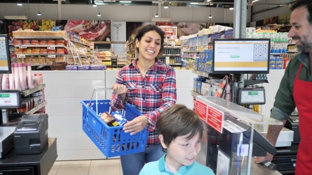 stockvideo's en b-roll-footage met latin familie winkelen in supermarkt-volwassen vrouw betalen met contactloze kaart - alleenstaande moeder