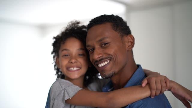 vídeos de stock, filmes e b-roll de pai latin que prende sua filha em casa-retrato - pai e filha