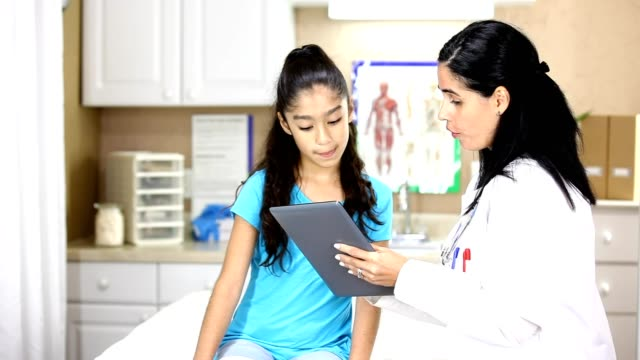 Latin female doctor holding digital tablet.  She is doing a sports check up on young Latin female patient. video