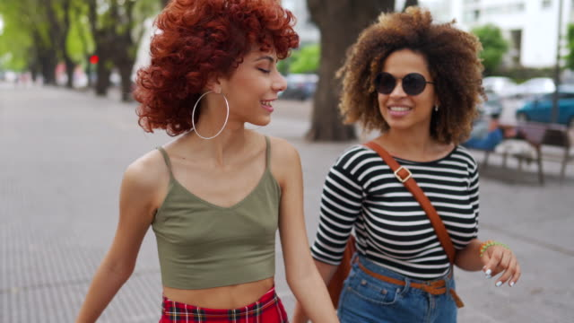 stockvideo's en b-roll-footage met latijnse vrienden die van mooie dag bij stad genieten - street style