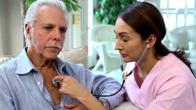 Latin Healthcare Professional Listens to Heart of Senior Man video