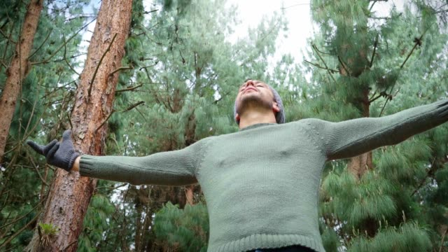 Latin man in the middle of the forest surrounded by trees, breathing the pure air of the forest while he opens his arms and enjoys nature. (slow motion)