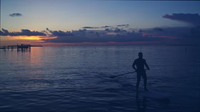 Latin man paddle boarding at dusk