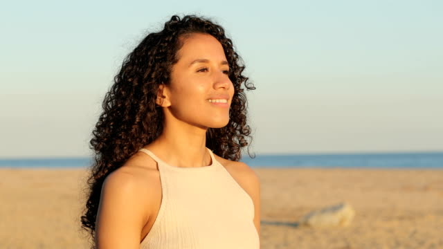 latin kadın sahilde temiz hava soludu - mindfulness stok videoları ve detay görüntü çekimi