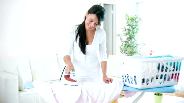 Latin woman ironing clothes at home - Vidéo