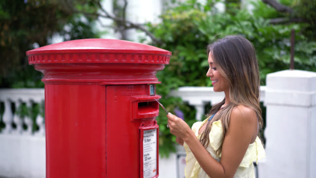 latin woman putting a letter in a traditional post box in london - inviare video stock e b–roll