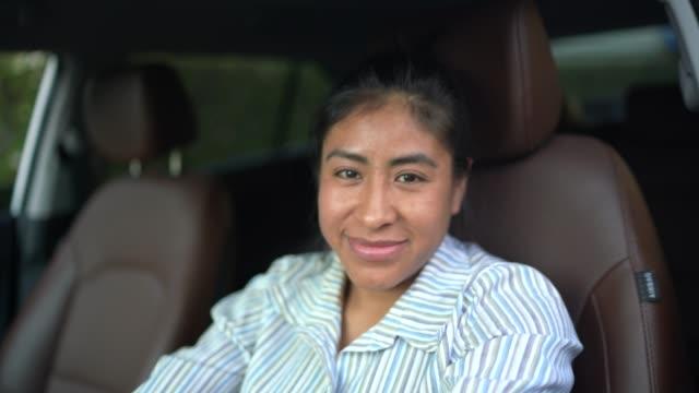 vídeos y material grabado en eventos de stock de mujer latina sentada en el asiento del conductor, conduciendo coche - uso compartido del coche