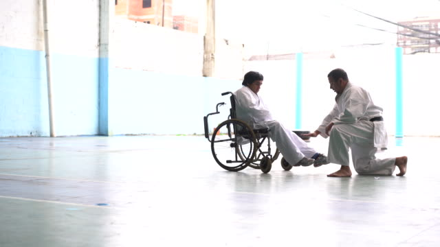 Latin young adult men in a wheelchair practicing parakarate poses with his teacher