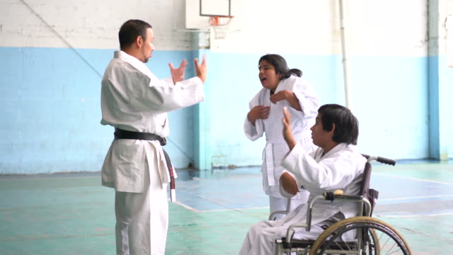 Latin young people with disability practice parakarate with their teacher