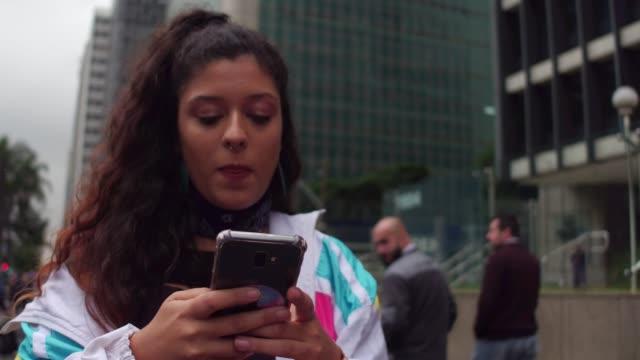 giovane donna latina che usa il cellulare durante l'ora di punta - argentina america del sud video stock e b–roll