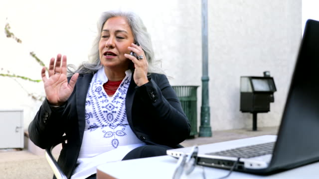 Latina Businesswoman Using Laptop at Cafe A businesswoman using a laptop and smartphone at cafe baby boomers stock videos & royalty-free footage