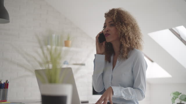 latina leadership: businesswoman working in her office. - owner laptop smartphone video stock e b–roll