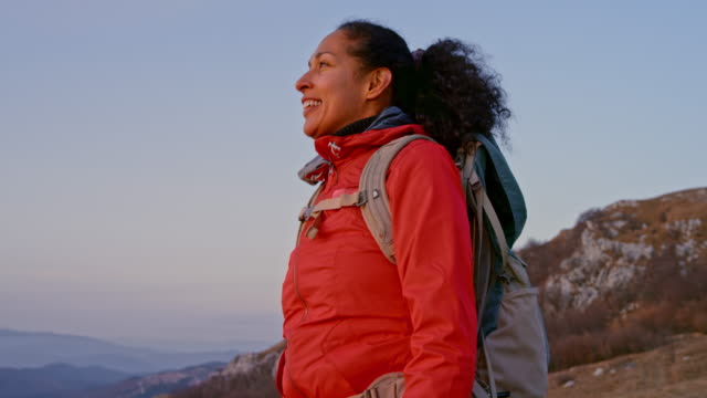 SLO MO Latin-American female hiker smiling as she reaches the mountain top at sunset