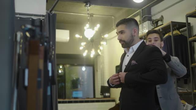vídeos y material grabado en eventos de stock de hombre latinoamericano se prueba un traje nuevo en la tienda de ropa masculina - bien vestido