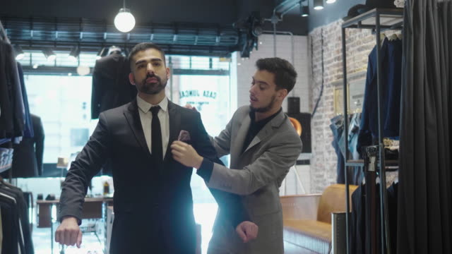 Latin-American man tries on a new suit at the menswear store Video series of a typical day at menswear store where young store manager does daily chores and interacts with customer. Shot in Buenos Aires. business suit stock videos & royalty-free footage