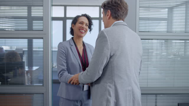 SLO MO Latin-American woman and Caucasian man shaking hands in the office and walking to the meeting room Slow motion wide shot of a Latin-American woman shaking hands with a Caucasian man before going into the conference room. Shot in Slovenia. businesswear stock videos & royalty-free footage