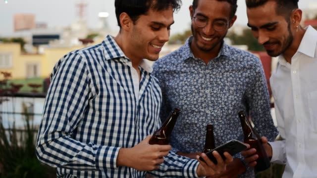 Latino and African-American men drinking beer at the rooftop party