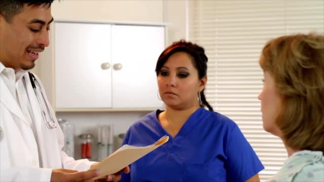 latino врач разговаривает с зрелой пациента - ассистент стоковые видео и кадры b-roll