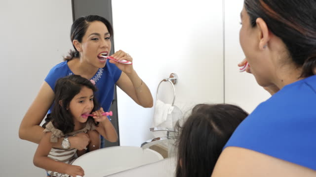 latino girl brushing teeth with parent - bagno domestico video stock e b–roll