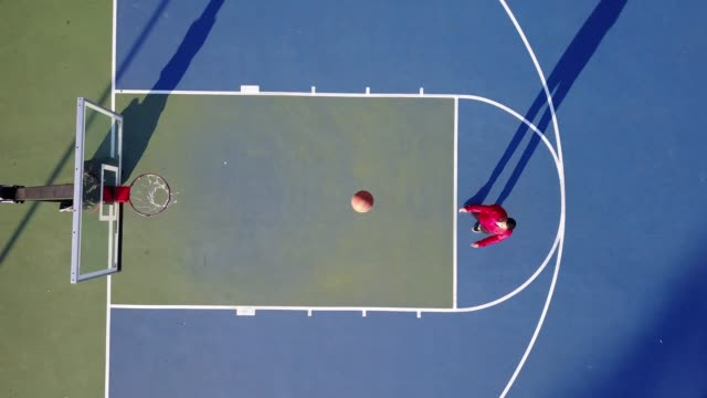 Latino guy shooting basketball on the court in USA in summer - drone footage Exercising for healthy lifestyle in USA basketball stock videos & royalty-free footage