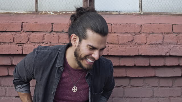 Latino handsome man laughing against a red brick wall Latino handsome man laughing against a red brick wall. handsome people stock videos & royalty-free footage