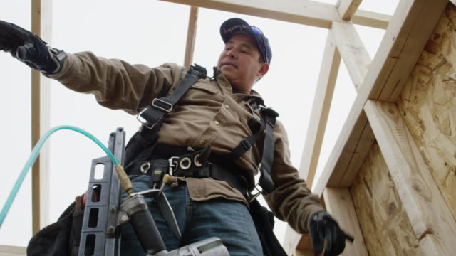 a latino man in his forties standing on construction framing and uses a level to make sure the wall is level in winter under an overcast sky - intelaiatura video stock e b–roll