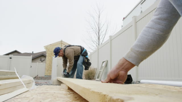 vídeos de stock e filmes b-roll de a latino man in his forties uses a circular saw to cut a wooden plank as another person secures the board on a construction site in winter under an overcast sky - cercado