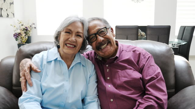 Latino senior couple hugging and sitting on couch