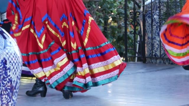 latynoskie kobiety w kolorowych tradycyjnych sukienkach tańczących jarabe tapatio, meksykański narodowy taniec kapelusza ludowego. uliczne wykonanie kobiecego baletu latynoskiego w wielokolorowych etnicznych spódnicach. dziewczyny w kostiumach - tradycja filmów i materiałów b-roll