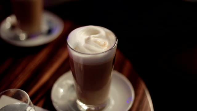 Latte on the table being stirred by a female hand video