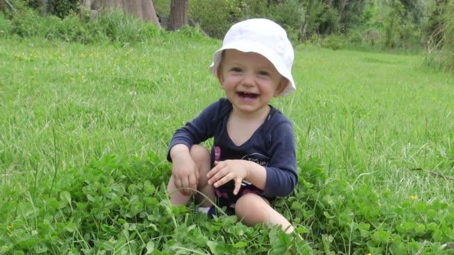 vidéos et rushes de rire bébé ramper dans l'herbe sur la journée d'été ensoleillée - ramper