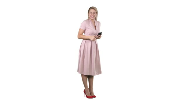 Laughing beautiful young woman in pink dress standing on white background