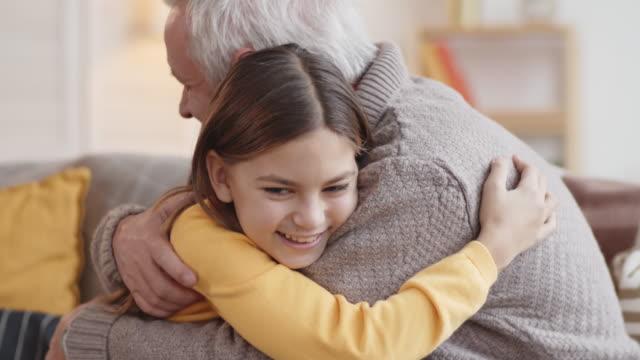 stockvideo's en b-roll-footage met lachen kaukasische meisje knuffelen opa thuis - omhelzen