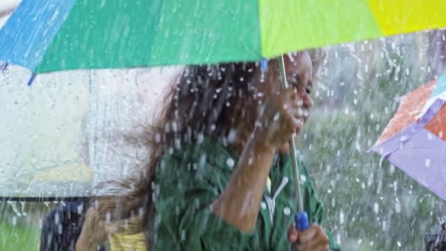 vídeos de stock e filmes b-roll de laughing children jumping in rain - guarda chuva