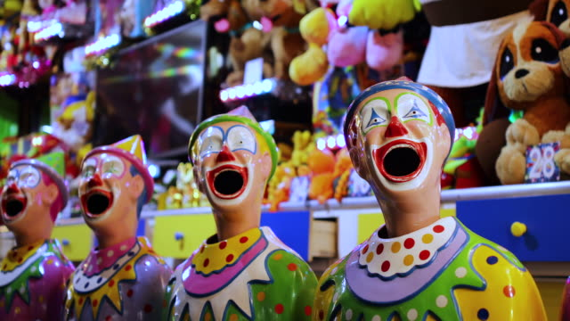 laughing clowns in sideshow alley at local fair - circus стоковые видео и кадры b-roll