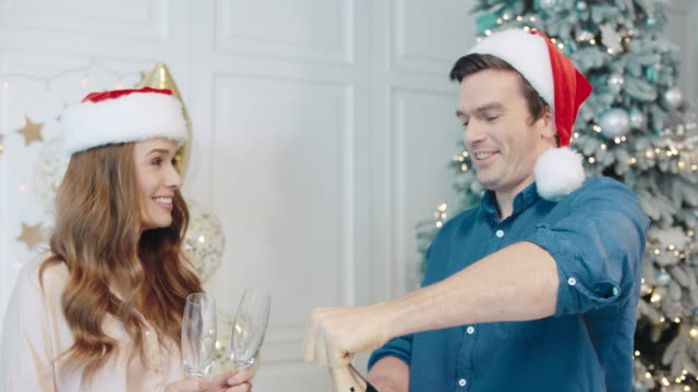 Laughing couple celebrating new year with sparkling wine.