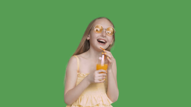 laughing girl holding in hands orange juice glass on transparent green background. happy girl teenager in yellow glasses with orange cocktail on green background. alpha channel, keyed green screen - healthy green juice video stock e b–roll